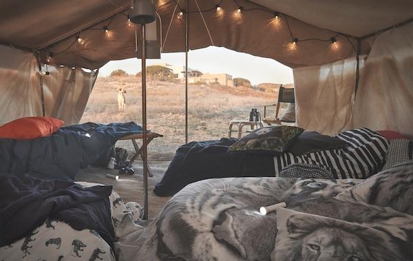 Linge de lit orné d'imprimés animaliers garnissant des lits sous une tente, dans le désert.