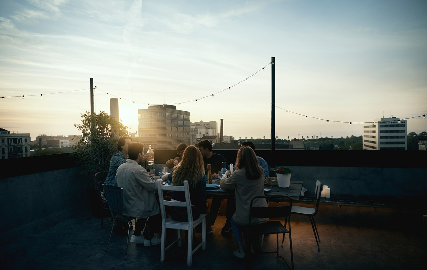 Link to 'a better world starts at home' IDEA - image of a group of friends gathered around a rooftop table at sunset.