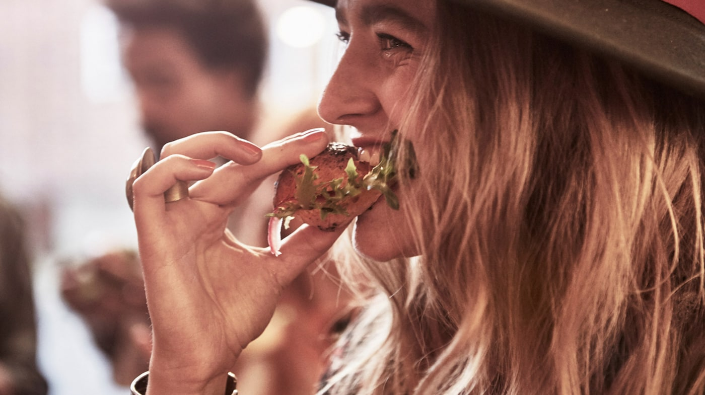Link to 'Delicious food you can trust' - image of woman taking a bite of a pulled salmon sandwich.