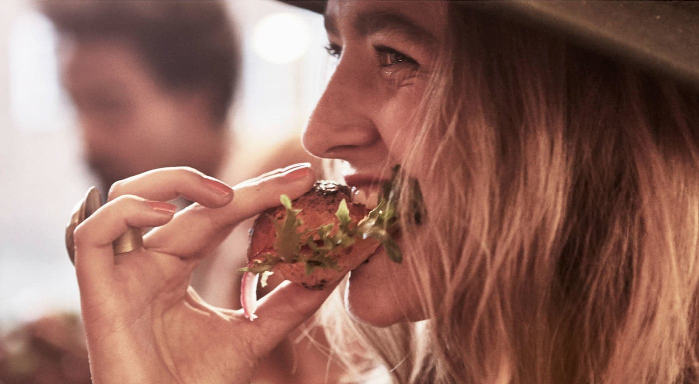 Link to Healthy Living - image of a woman taking a bite of a pulled salmon sandwich.