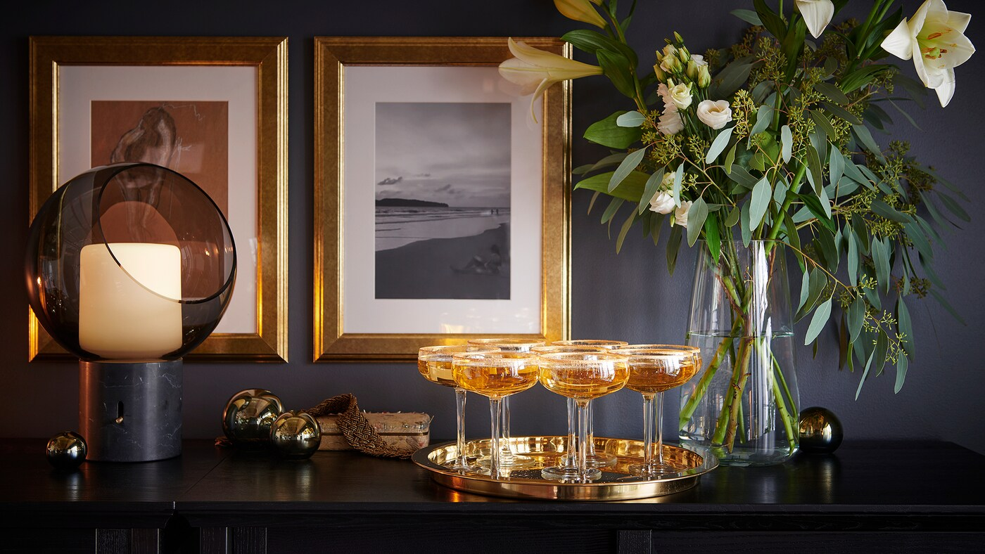 Link to 'Let your home sparkle and pop' - image of a sideboard with a golden tray filled with champagne glasses.