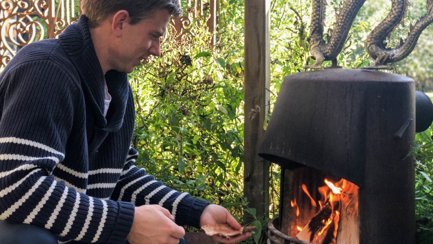 Link to 'Life at home in extraordinary times – Part 3: Shared experiences' - image of a man wearing a navy blue sweater with white stripes, making a fire in a fireplace.