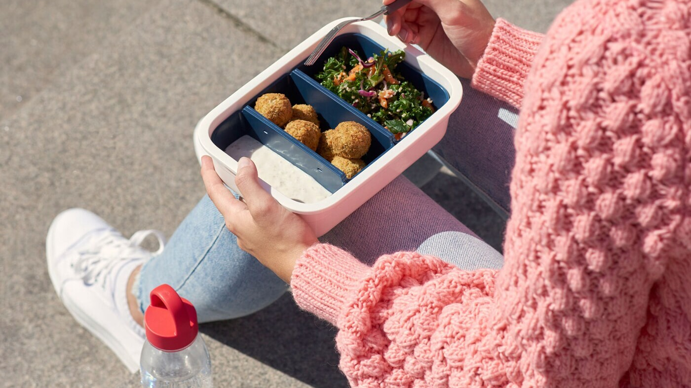 Link to 'Only recycled or renewable based plastic in IKEA products by 2030' - image of a woman eating from an IKEA plastic food container.
