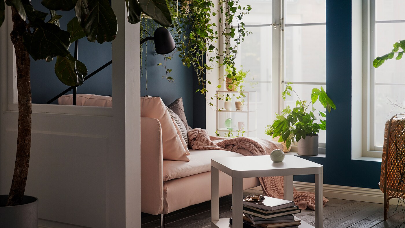 Link to 'Tips on how to increase your living room well-being with plants' - image of a living room with large windows, a pink chaise lounge, and lots of plants.