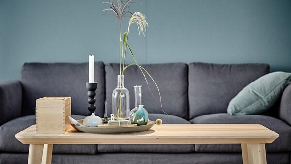 LISABO stůl z jasanové dýhy s dekorací na povrchu umístěný před šedou pohovkou. Stůl získal prestižní cenu za design Red Dot Award.