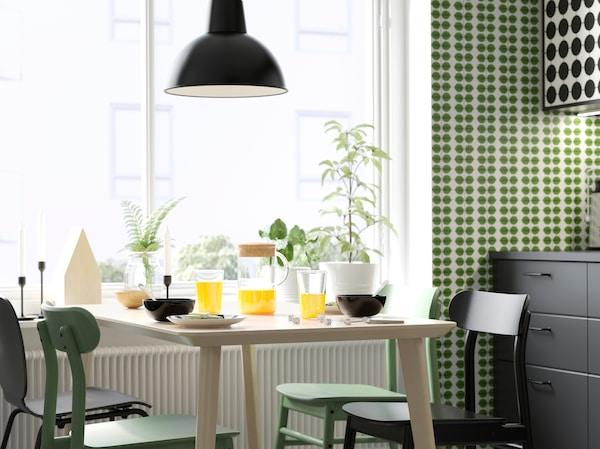 LISABO طاولة طعام بقشرة خشب الدردار الفاتح من ايكيا ومقاعد RÖNNINGE خضراء وكراسي SVENBERTIL سوداء في غرفة الطعام.