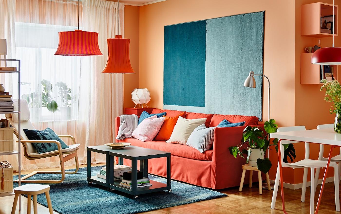 Lisää moderniin olohuoneeseen räiskyviä värejä. Kolmen istuttava IKEA BRÅTHULT-sohva, jossa on punainen tai oranssi Vissle-päällinen, oranssi seinä ja sininen IKEA SÖNDERÖD-matto.