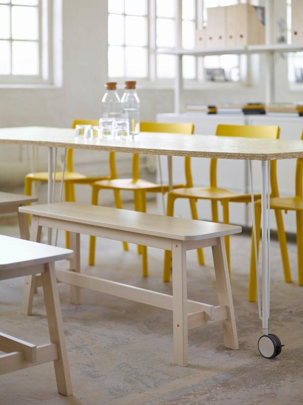 Lisää vain mukavat työkaverit. IKEA NORRÅKER valkoinen koivupenkki. IKEA JANINGE keltainen ruokapöydän tuoli. IKEA 365+ karahvi ja korkki, kirkasta lasia.