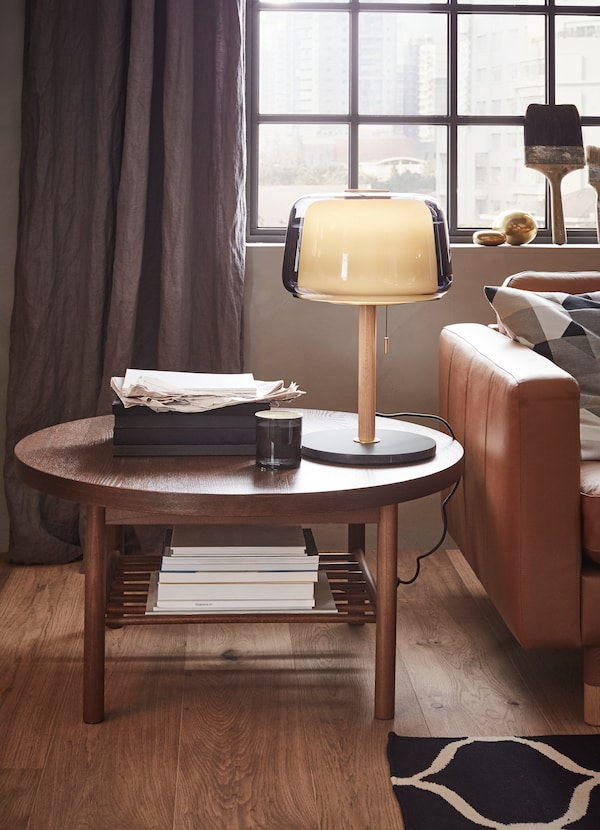 LISTERBY round dark wooden coffee table with a lamp and papers on top by the sofa.