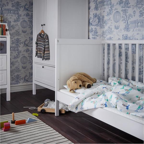 Lit bébé blanc avec du linge de lit blanc/à motif et un chien en peluche, des jouets en bois au sol, une garde-robe en arrière-plan.