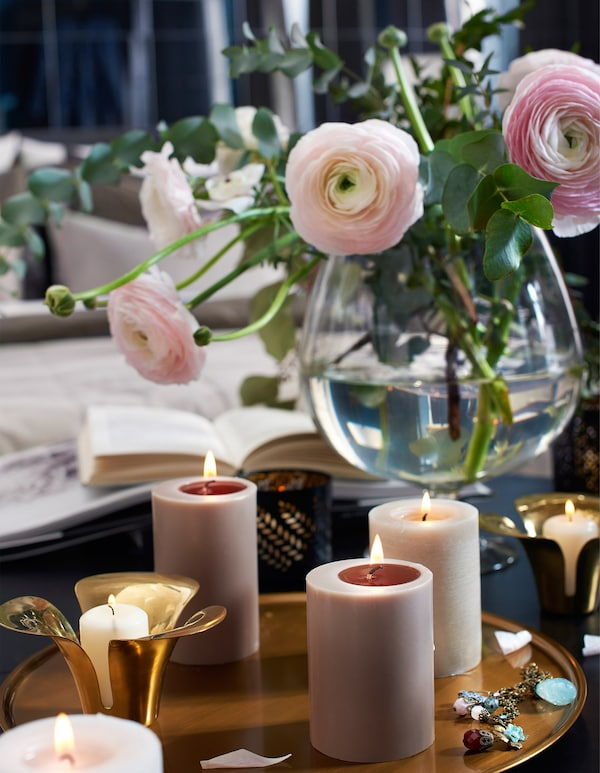 Lit candles and fresh flowers on a bedroom table.