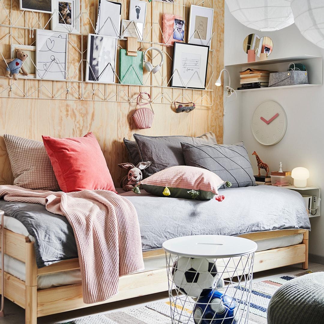 Lit d'appoint en bois dans une chambre d'adolescent, textiles colorés et images disposées sur des tableaux-mémo installés au mur.