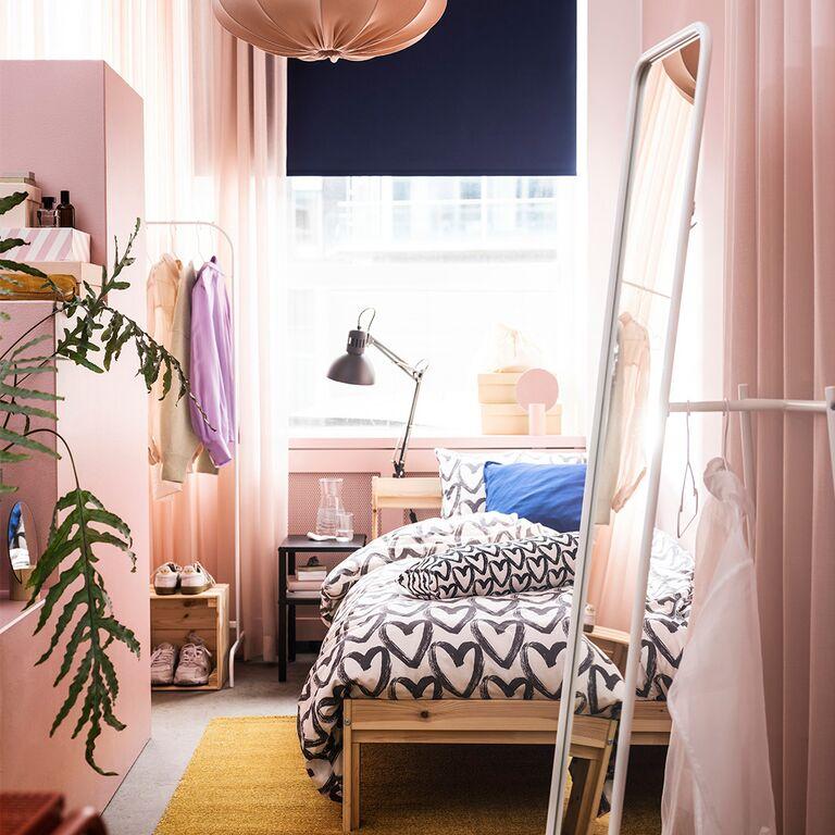 Lit d'appoint, miroir sur pied et portant dans une petite chambre rose.