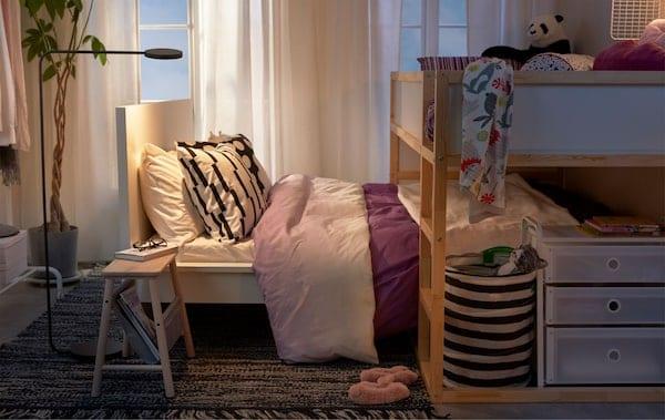 Lit haut pour enfant placé perpendiculairement au lit des parents dans une petite chambre à coucher.