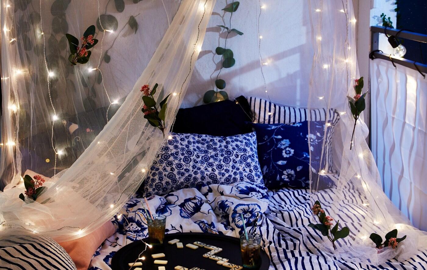 Lit installé sur le balcon, dais-moustiquaire garni de fleurs et de guirlandes lumineuses à DEL, boissons et jeux sur un plateau.