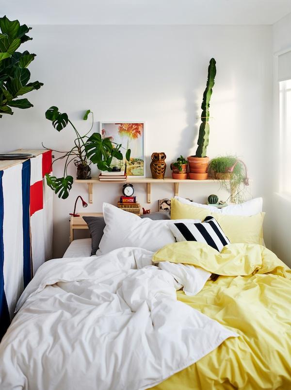 Lit NEIDEN avec deux ensembles de linge de lit ÄNGSLILJA, un jaune et un blanc. Plantes et décorations sur une tablette au-dessus du lit.