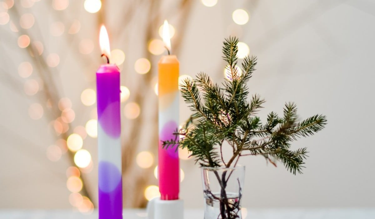 Lit purple, pink, and orange dip-dyed candles  in white candle-holders