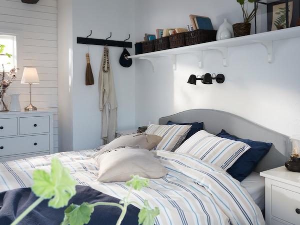 Lit rembourré IKEA HAUGA beige avec housse de couette et taies d'oreiller à rayures et deux appliques noires montées sur le mur au-dessus du lit.