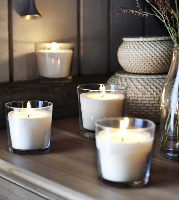 Lit vanilla-scented candles in glass cups sit in a rustic-style bedroom.