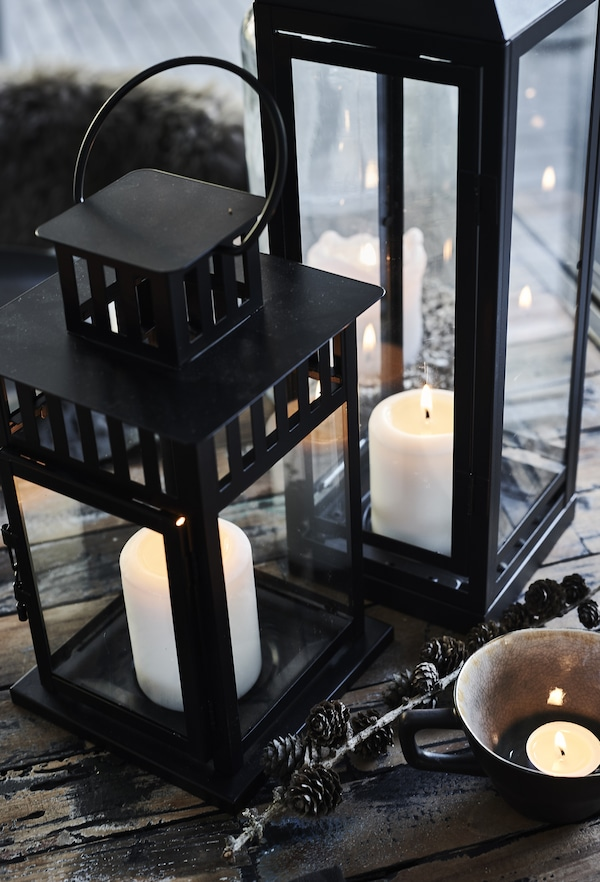 Lit white block candles in large black lanterns on the table.