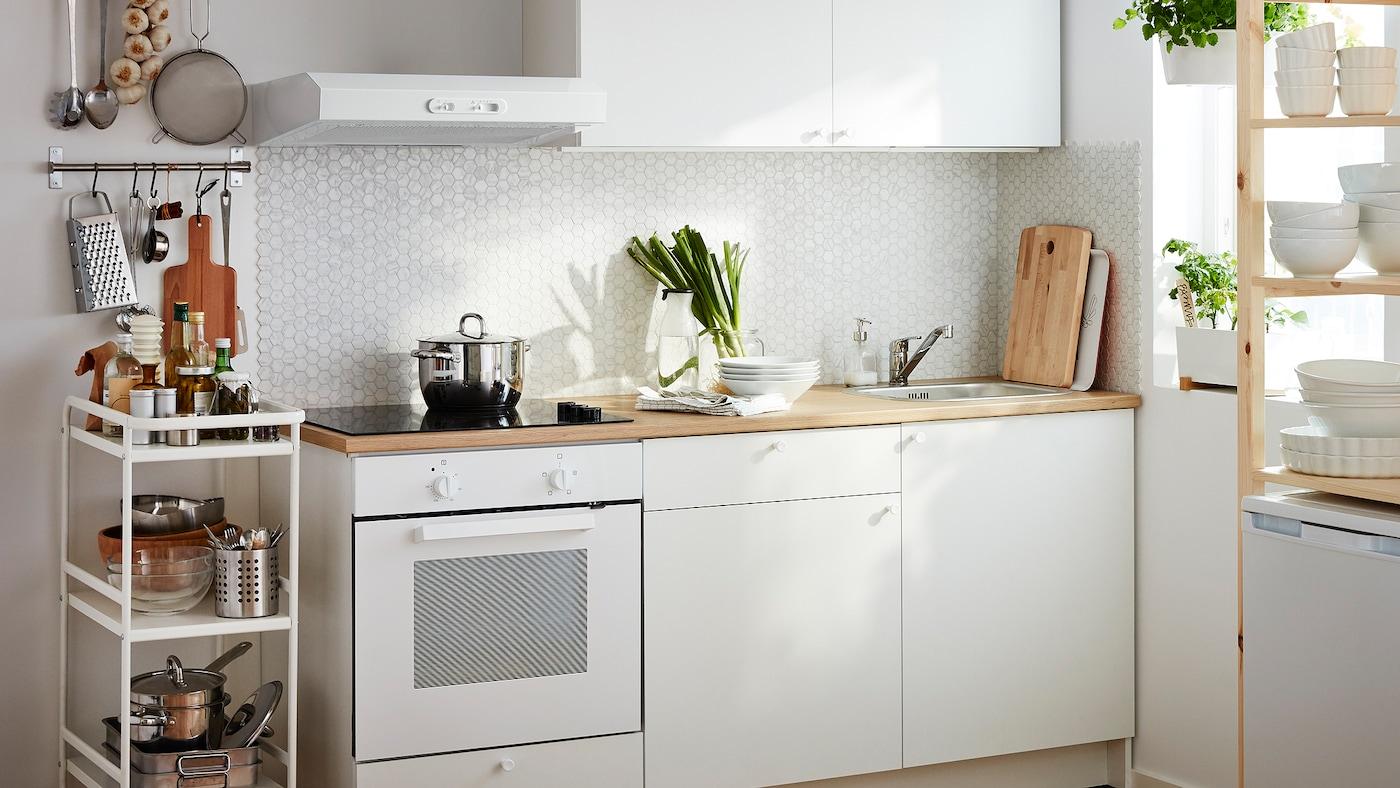 Lite, hvitt kjøkken med integrert stekeovn og benkeskap, skuffer, benkeplate og veggskap.