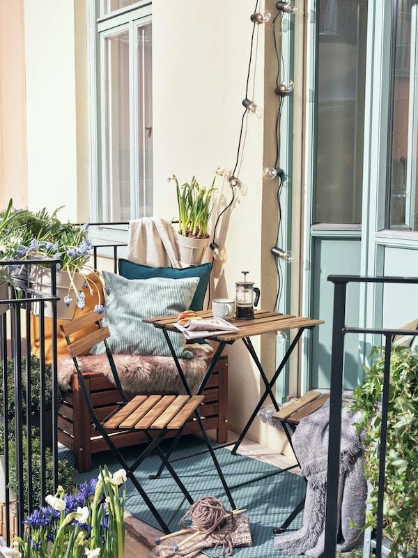 Liten balkong med fällbara slolar och bord.