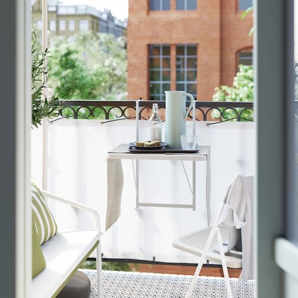 Liten balkong med hvit skjerm rundt svarte rekkverk, en hvit stol og et bord med ei flaske og en termos.