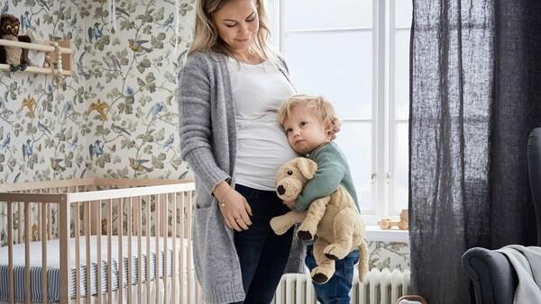 Liten gutt koser med mammas gravide mage.