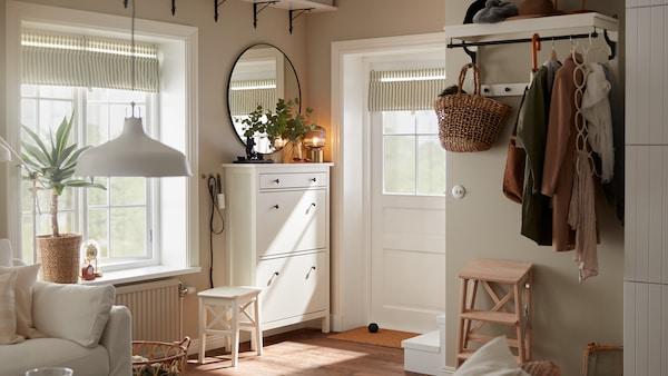 Liten hall med vit dörr, vitt skoskåp, rund spegel, vit hatthylla med jackor och ett paraply.