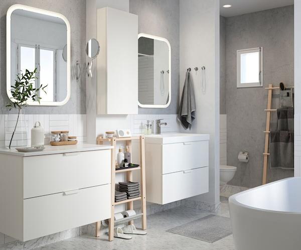 Litet badrum med dusch, vita möbler, vitt kakel, mörkblå väggar, rosa badrumsmatta, spegelskåp och blå handdukar.