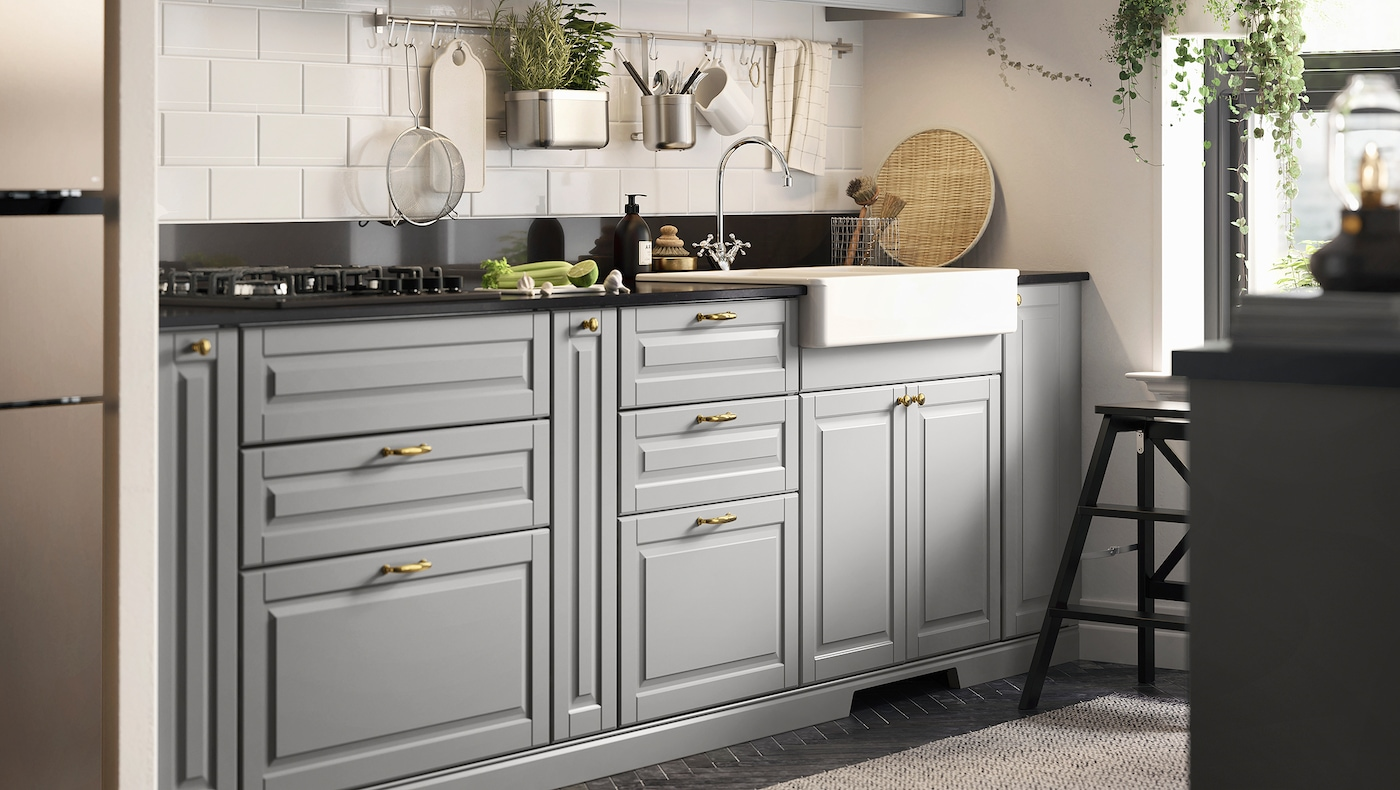 Litet kök med grå köksskåp, svart mineralmönstrad bänkskiva, vit diskho med synlig front och en gashäll.
