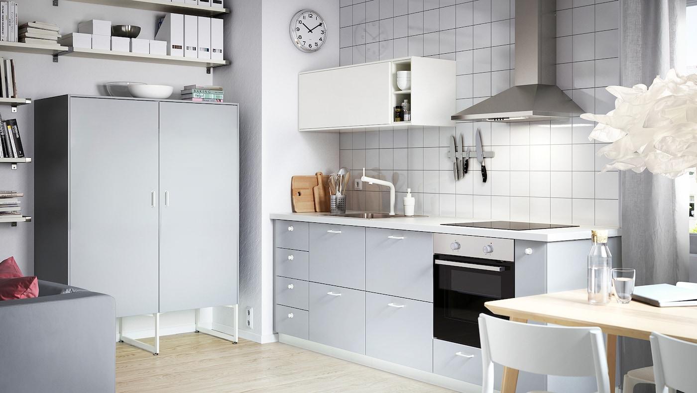 Litet kök med skåp med grå lådfronter, vitt väggskåp och grått väggskåp med luckor.