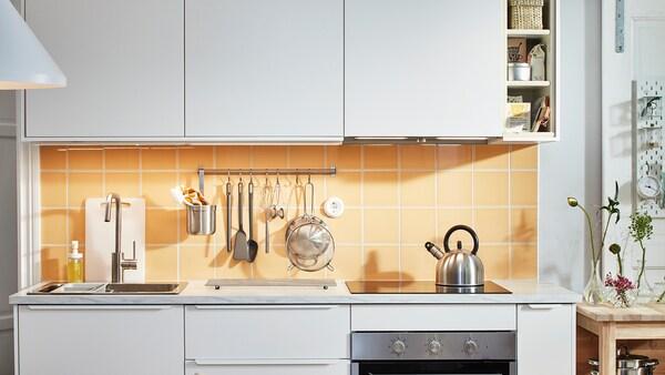 Litet vitt kök med vita VEDDINGE luckor och orangegult kakel, häll samt stång med diverse köksredskap.