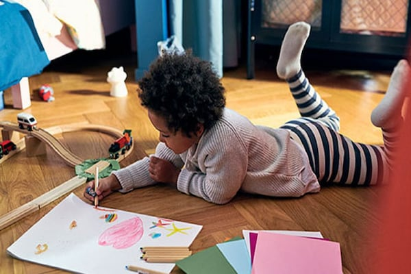 little girl laying on the floor coloring surrounded by toys and craft supplies