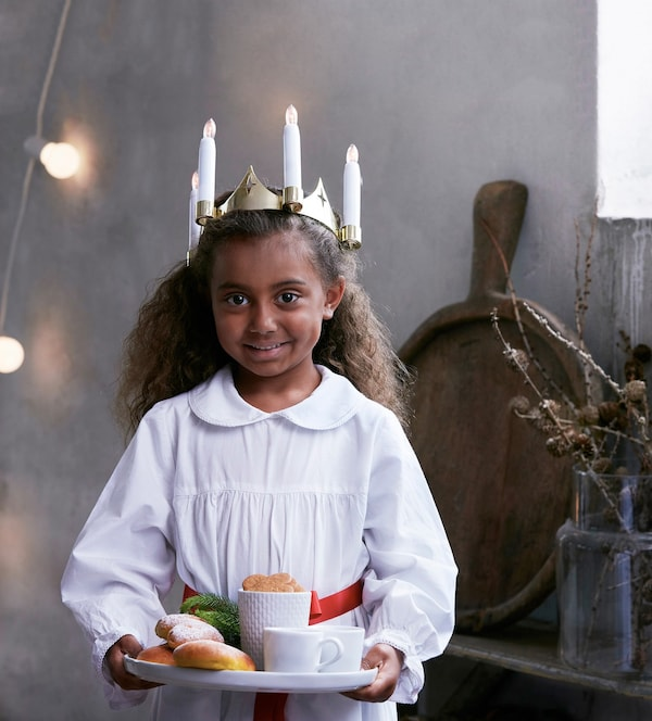 Little girl wearing a white dress and a crown with candle lights, holding a plate with safran buns, cookies and tea cups