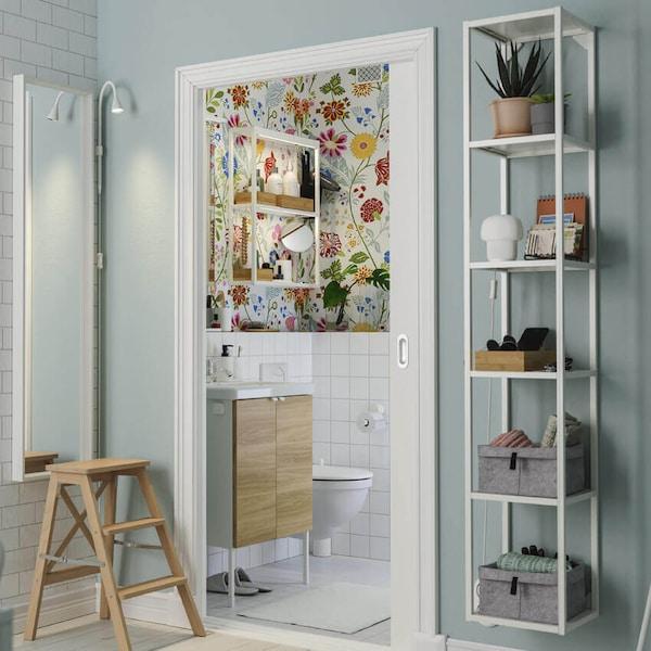 Liukuovi avautuu keittiöstä värikkääseen kylpyhuoneeseen, jossa on kukkatapetti ja pieni pesuteline.
