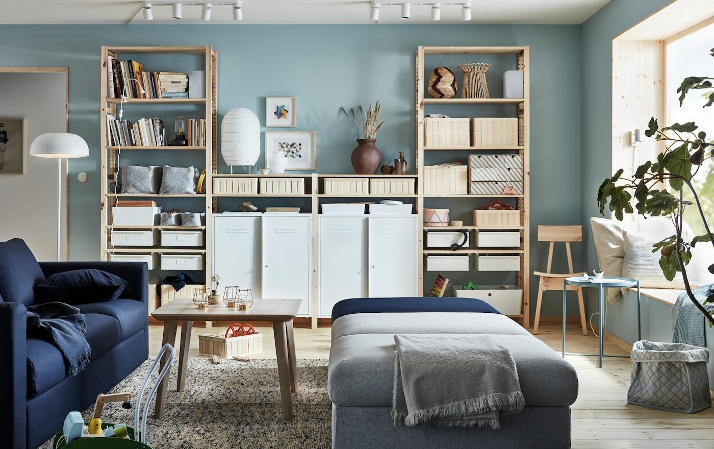 Living donde hay un sofá azúl oscuro VIMLE, una mesa de centro de madera y módulos de sofá grises y azul para sentarse. Un mueble grande atrás de madera lleno de libros y cajoneras organizadoras.
