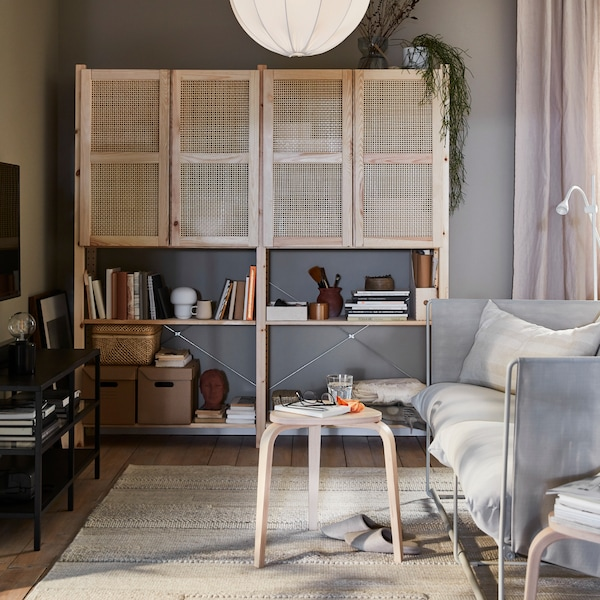 Living room corner with a sofa facing a wall-mounted TV. An IVAR storage unit with mesh doors stands along the other wall.
