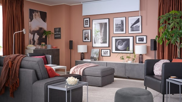 Living room decorated in pink hues with grey furniture.