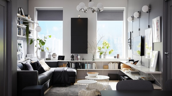 Living room with a black sofa-bed with chaise longue, white shelves, a wall-mounted cabinet and a dark grey rug.