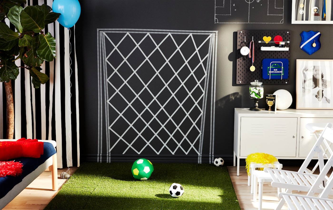 Living room with a tape-on-the-wall football goal, a patch of artificial grass, balls, seating and supporter paraphernalia.