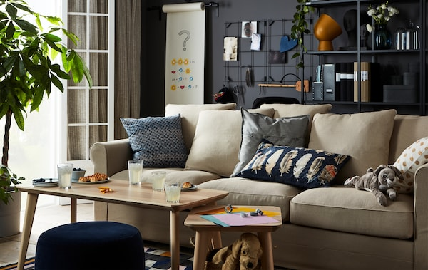 Living room with sofa and coffee table, with an ongoing origami-folding and drinks-and-snacks session.
