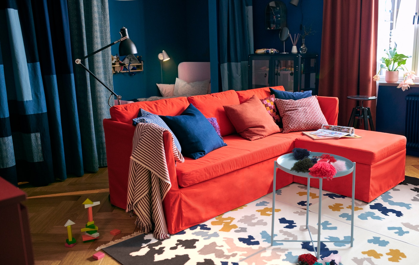 Living small? Place a sofa-bed in the middle of the room for more wall storage space. Try IKEA BRÅTHULT red-orange sofa bed!