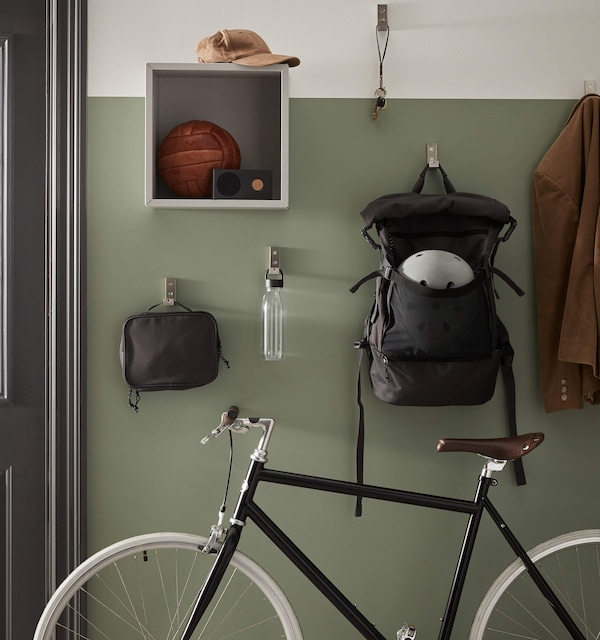 Living space entryway with bicycle, bag and various shelves holding everyday essential items