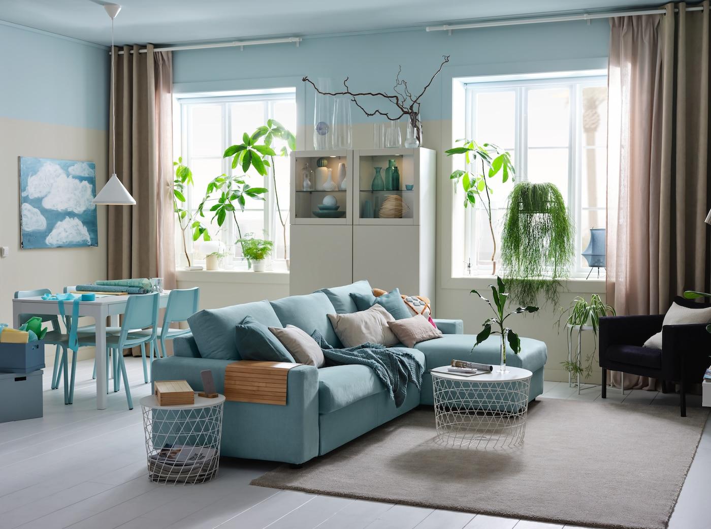 Ljust rum med 3-sitsbäddsoffa med schäslong, vit förvaringskombination och en matplats.
