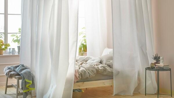 Ljust sovrum med en säng intill ett fönster. Sängen har en sänghimmel gjord av vita gardiner och VIDGA gardinskenor.