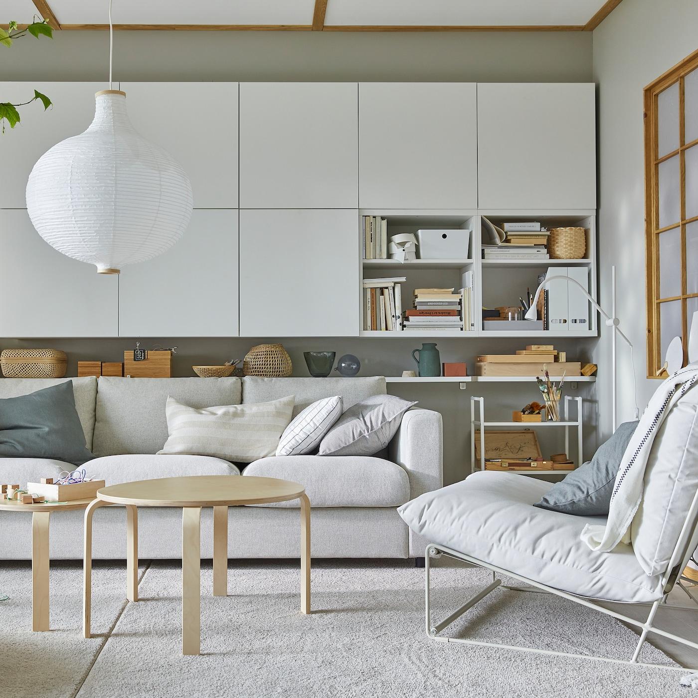 Ljust vardagsrum med HAVSTA fåtölj, många vita väggmonterade skåp och en rund, vit taklampa.