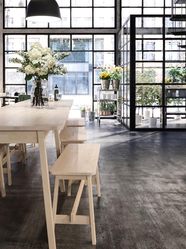 Locale con tavolo e sedie in legno, vaso di fiori sul tavolo, luci sospese e vetrate sullo sfondo.