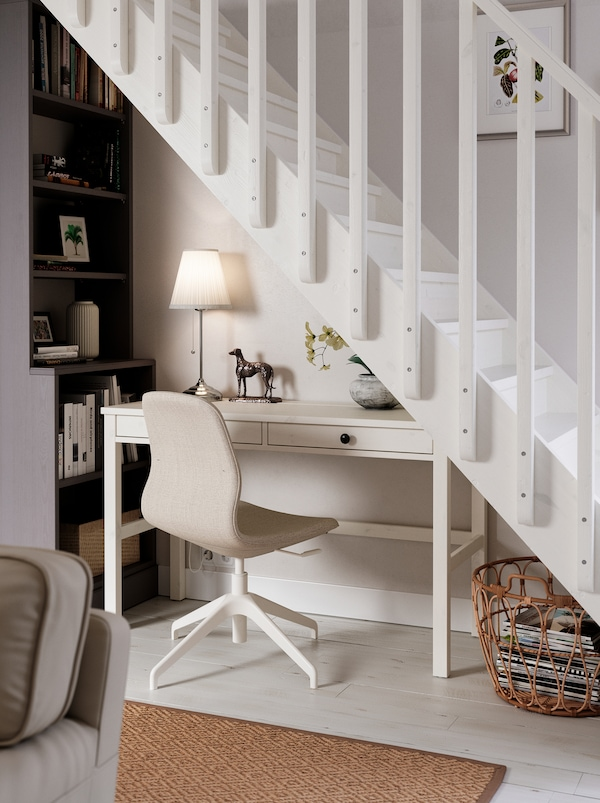 Located under a staircase is a workspace consisting of a white HEMNES desk, a LÅNGFJÄLL chair, a lamp and a tall bookcase.