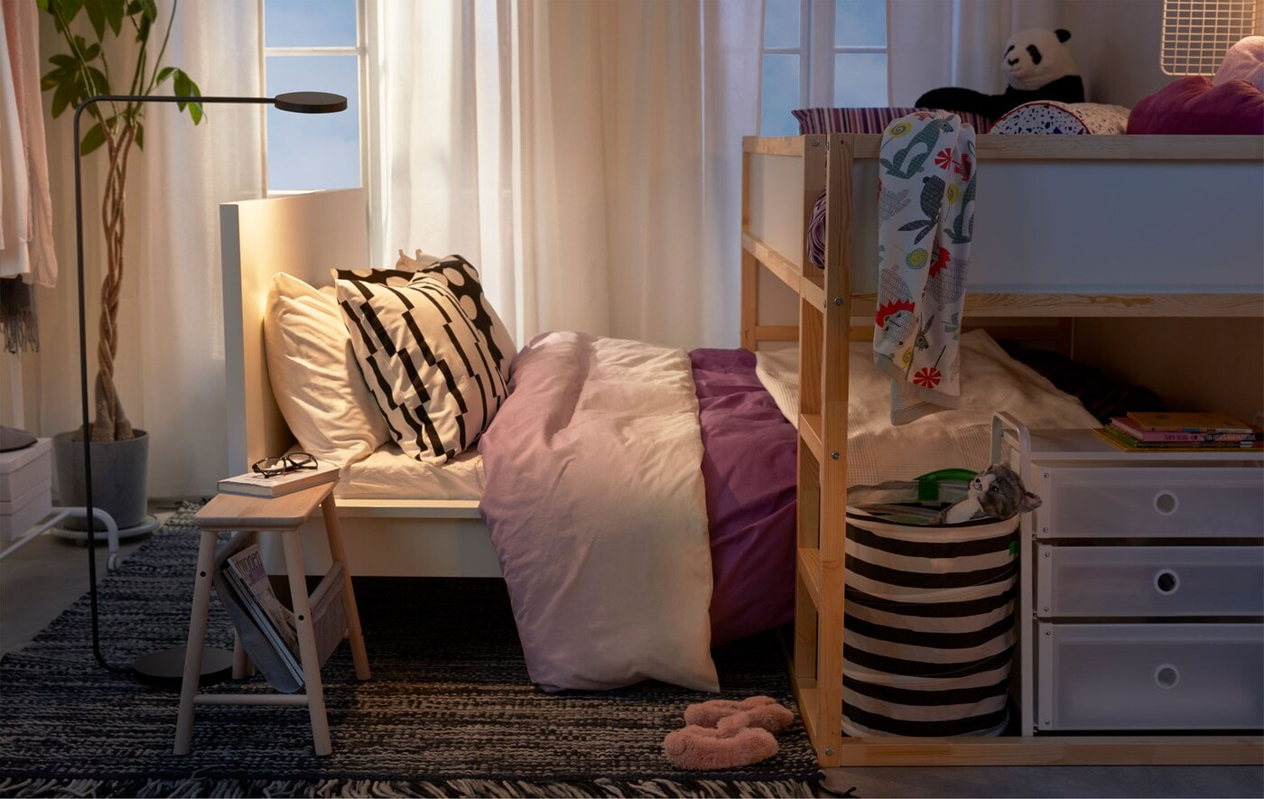 Loft bed standing across a lower bed, as a child's bed straddling the parents', in a small-space bedroom.